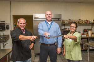 Lott Industries Chief Operating Officer Dan Clemens, center, with Pat Howard and Angela LaPlante at Lott Industries' kitchen. See article in Toledo Free Press, photo by Christie Materni.