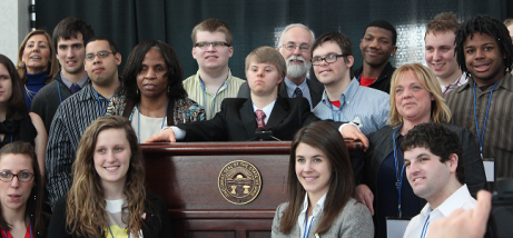 DODD Director John Martin steps to the podium with students in The Ohio State University TOPS program. Adam Moss (at podium) addressed nearly 600 attendees at the annual Developmental Disabilities Awareness and Advocacy Day, at the Ohio Statehouse. TOPS stands for Transition Options in Postsecondary Settings for students with intellectual and developmental disabilities.