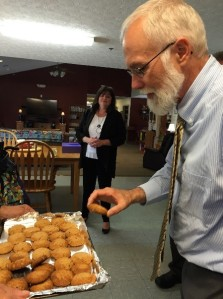 Director Martin has a cookie made by residents at Echoing Lake. Lorain County Superintended Amber Fisher in the background.