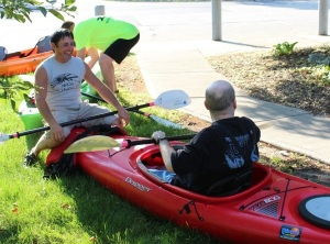 Individual sits in a kayak and learns to paddle.